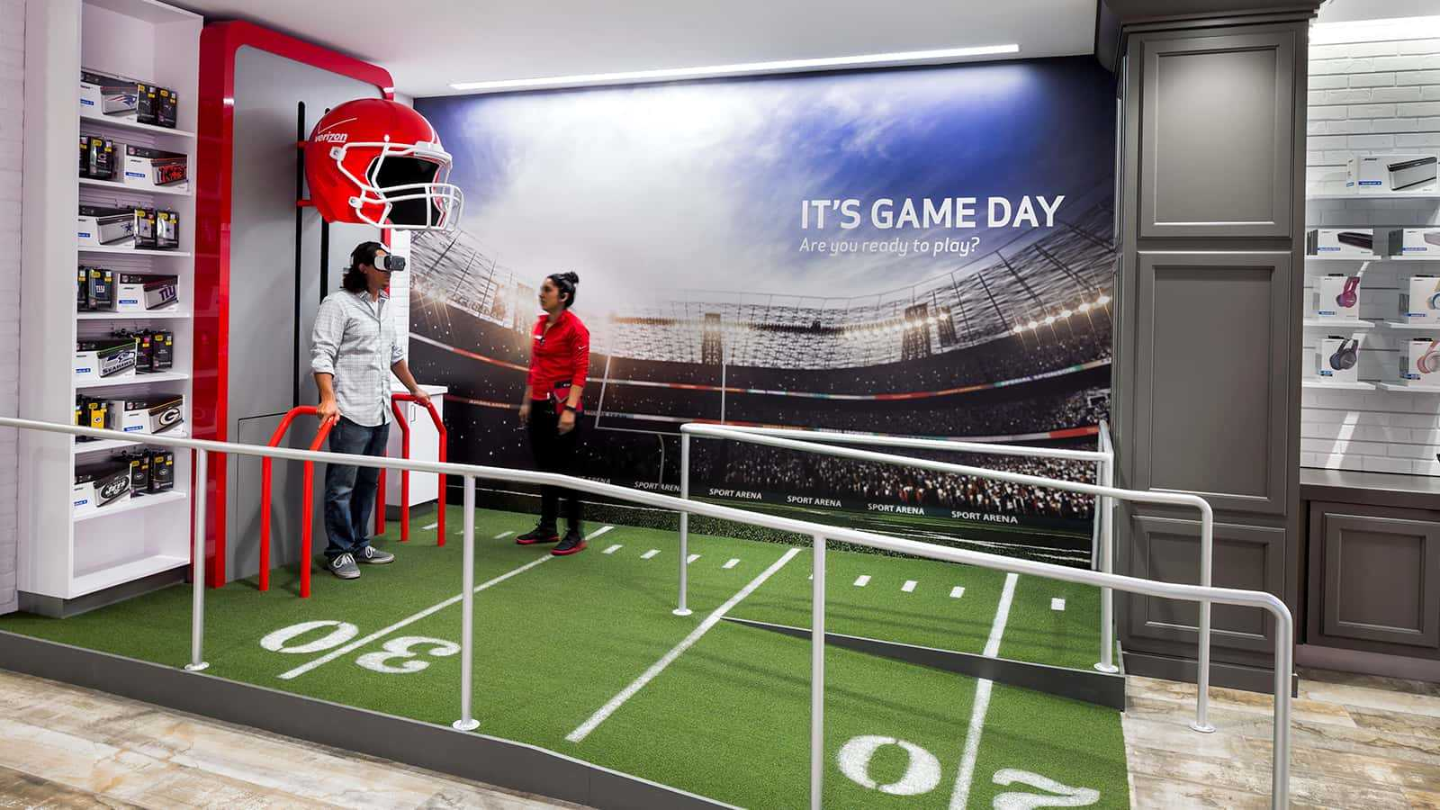 an employee showing a customer of a football virtual reality experience