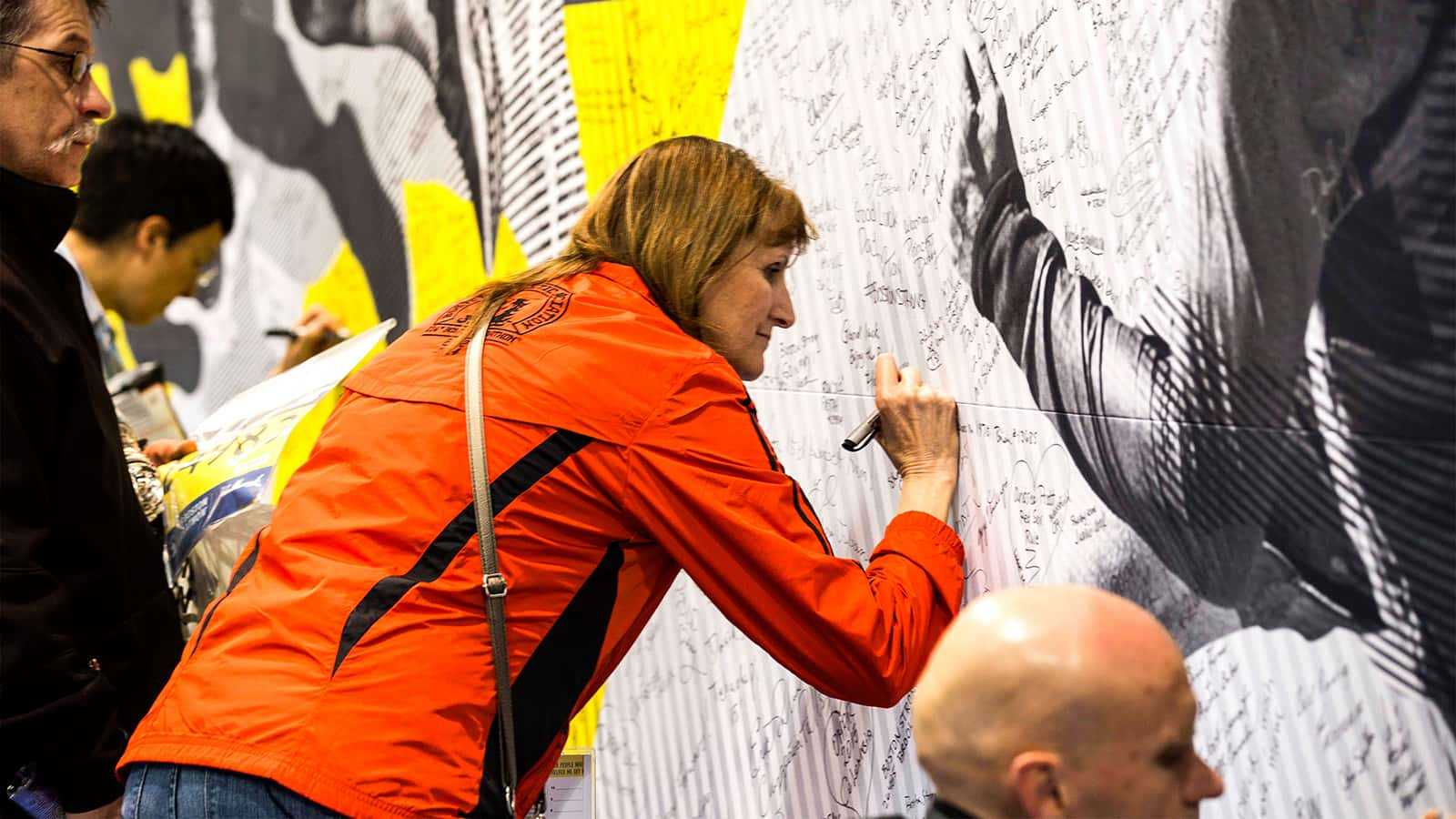 "alt=""Attendee signing wall at the adidas Boston Marathon store 2015."""